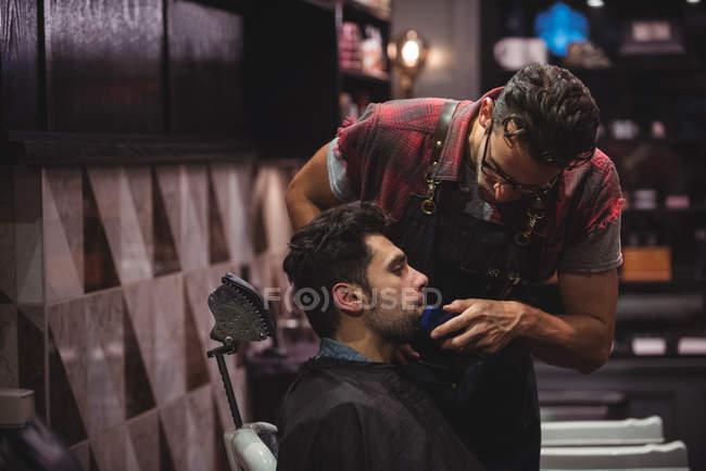 Клієнт отримання борода голені з Триммер в перукарні — стокове фото
