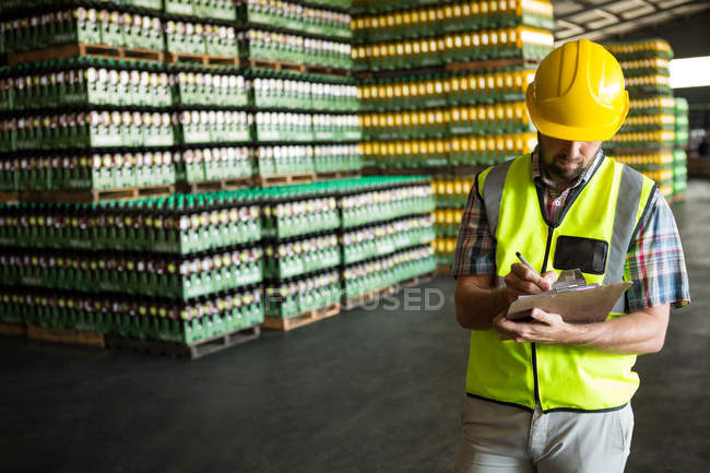 Male worker writing on clipboard in warehouse — Stock Photo