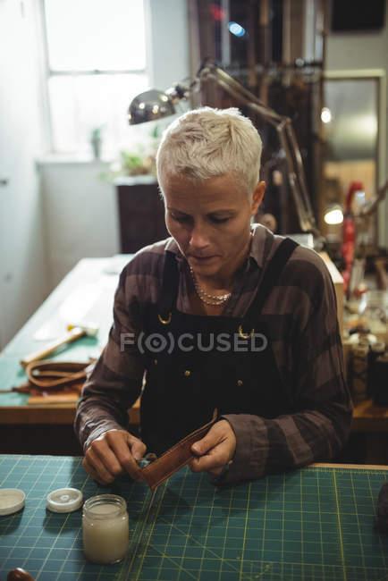 Atento artesão preparando cinto de couro na oficina — Fotografia de Stock