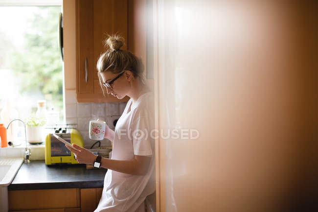 Woman using digital tablet while having coffee in kitchen at home — Stock Photo