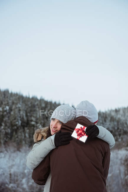 Happy couple embracing each other on snow covered mountain — Stock Photo