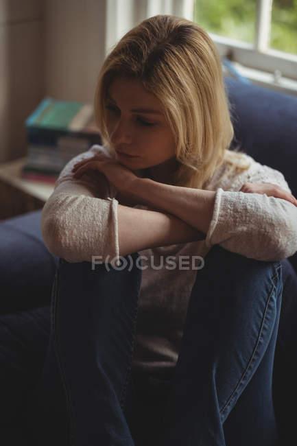 Задумчивая женщина сидит на диване в гостиной дома — стоковое фото
