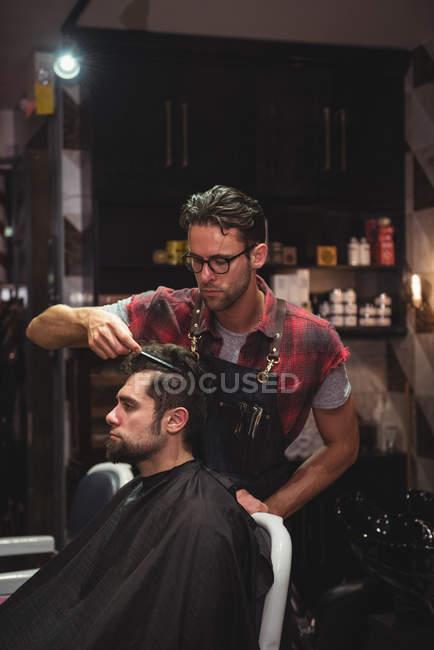 Parrucchiere pettinando i capelli del cliente nel negozio di barbiere — Foto stock