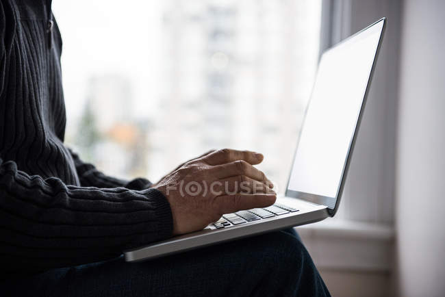 Mid-section of man sitting on bed and using laptop at home — Stock Photo