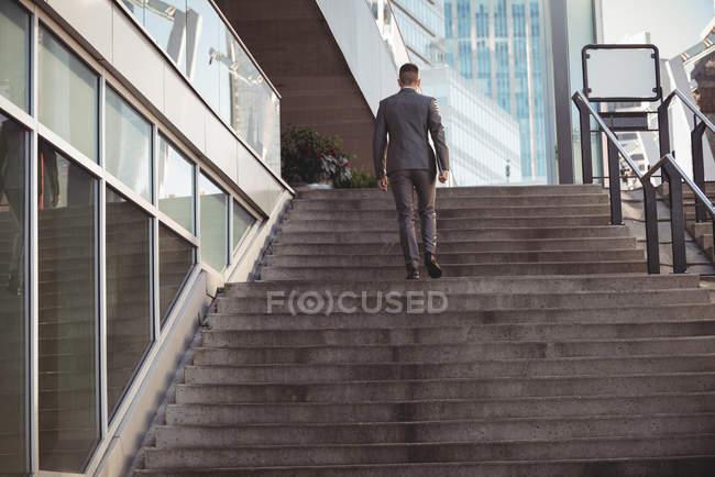 Задній вид бізнесмен з щоденник, піднімаючись сходи в Офісна будівля — стокове фото