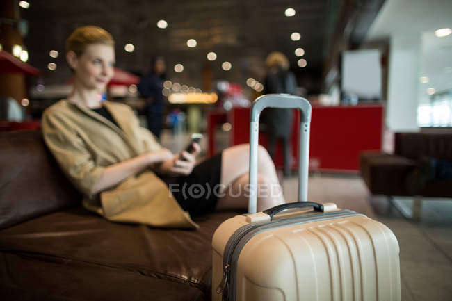 Businesswoman using mobile phone in waiting area at airport terminal — Stock Photo