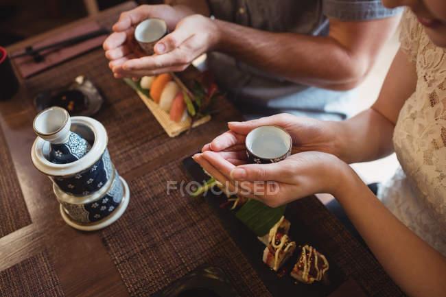 Paar trinkt Sake beim Sushi essen im Restaurant — Stockfoto