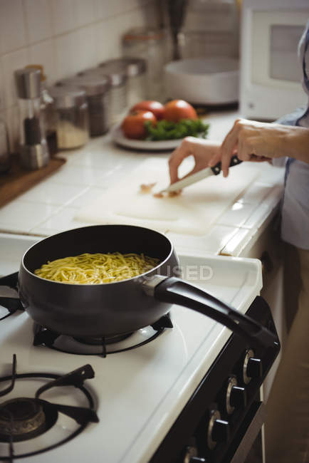 Mid section of woman cooking in kitchen at home — Stock Photo