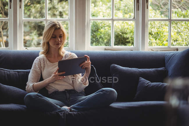 Beautiful woman sitting on sofa with digital table in living room at home — Stock Photo
