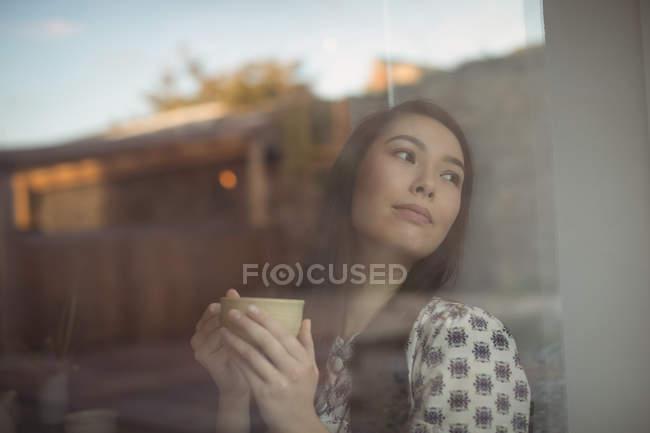 Продуманий одна жінка чашку кави біля вікна в кафе — стокове фото