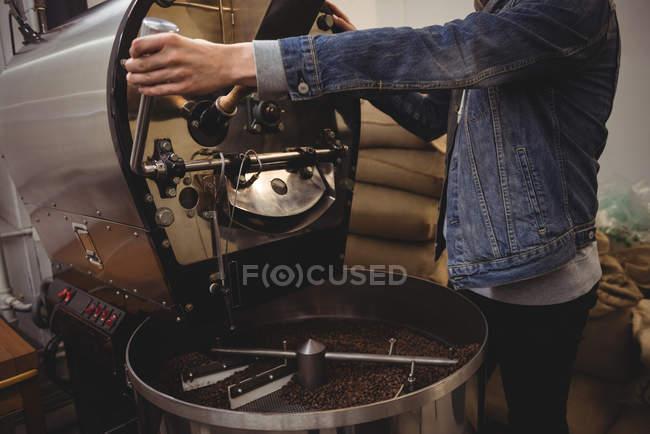 Man using coffee grinding machine in coffee shop — Stock Photo