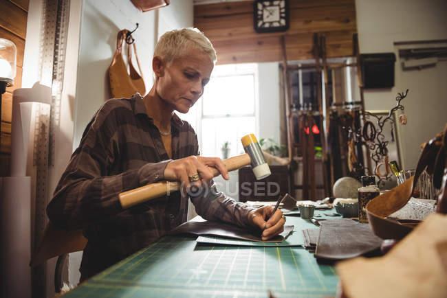 Внимательная ремесленница прибивает кожу в мастерской — стоковое фото