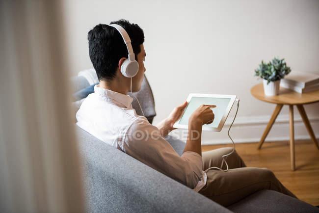 Mann hört zu Hause Musik auf digitalem Tablet — Stockfoto