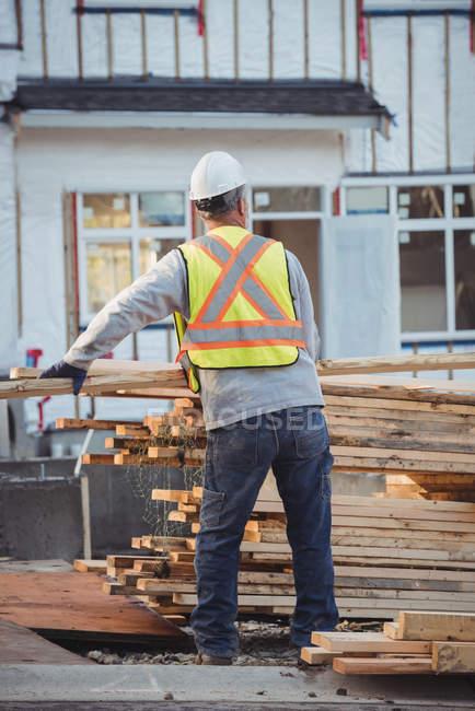 Строитель организует лесозаготовки на стройплощадке — стоковое фото