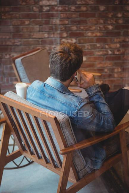 Vista posteriore dell'uomo che parla al telefono cellulare nel caffè — Foto stock
