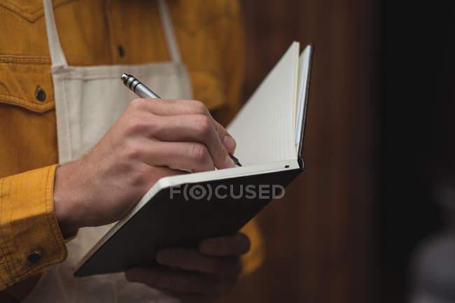 Close-up do homem escrever no livro de nota em casa cervejaria — Fotografia de Stock