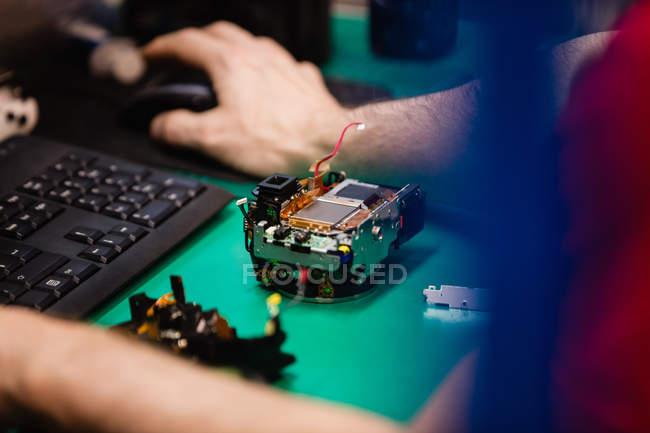 Nahaufnahme eines Mannes, der in einem Elektronikreparaturzentrum am Desktop-PC arbeitet — Stockfoto