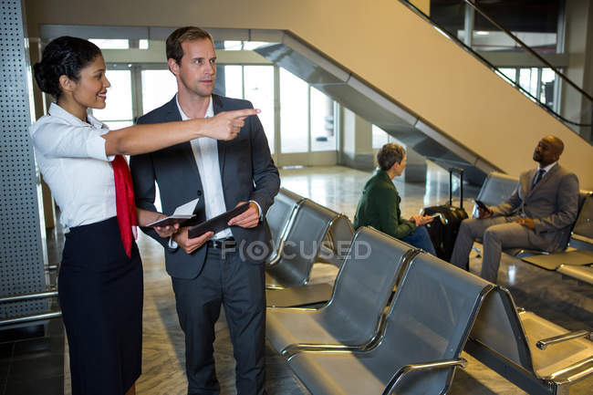 Женский персонал, показывая направление бизнесмен в аэропорту терминал — стоковое фото