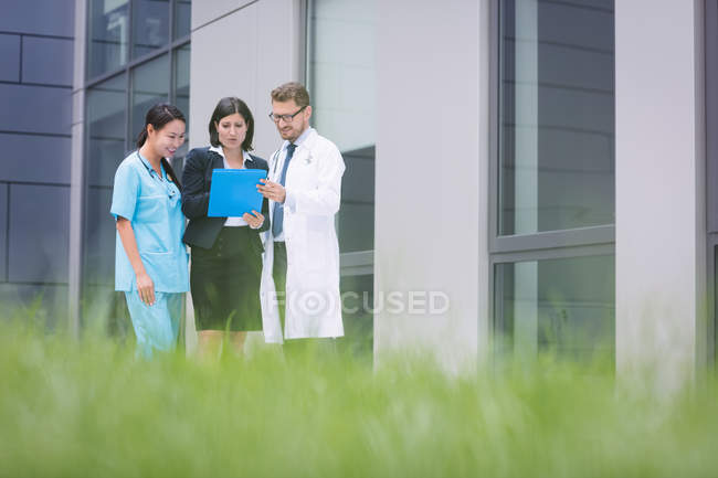 Médicos y enfermera discutiendo sobre informe en instalaciones del hospital - foto de stock