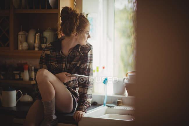 Frau mit digitalem Tablet schaut zu Hause durch Fenster in Küche — Stockfoto