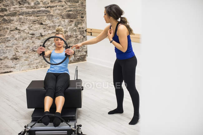 Женщина-тренер помогает женщине с тренировкой с пилатесом кольцо в тренажерном зале — стоковое фото