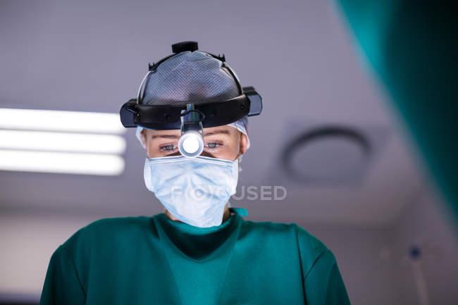 Femme chirurgien portant des loupes chirurgicales lors d'opération en théâtre d'opération — Photo de stock