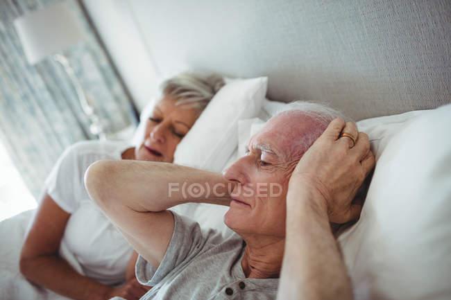 Último homem deitado na cama e cobrindo seus ouvidos com as mãos no quarto — Fotografia de Stock