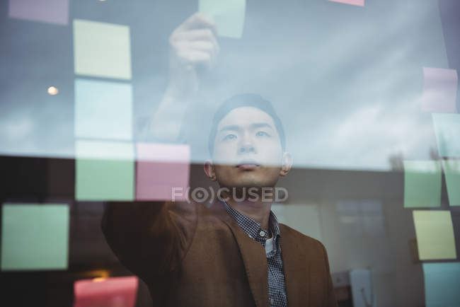 Business executive looking at sticky note in office — Stock Photo