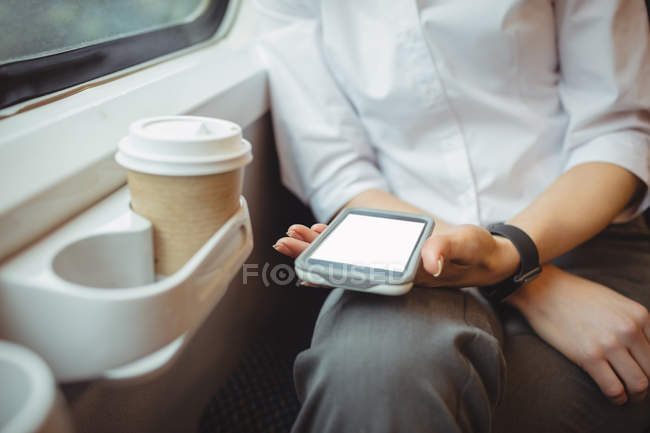 Средняя секция деловой женщины, держащей мобильный телефон во время путешествия — стоковое фото