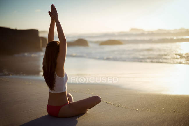 Beautiful woman performing yoga on beach on a sunny day — Stock Photo