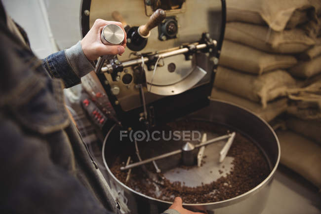 Mid-section of man grinding coffee beans in grinding machine in coffee shop — Stock Photo