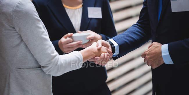 Розділ середині ділові люди вітають один одного під час перерви в офісі — стокове фото