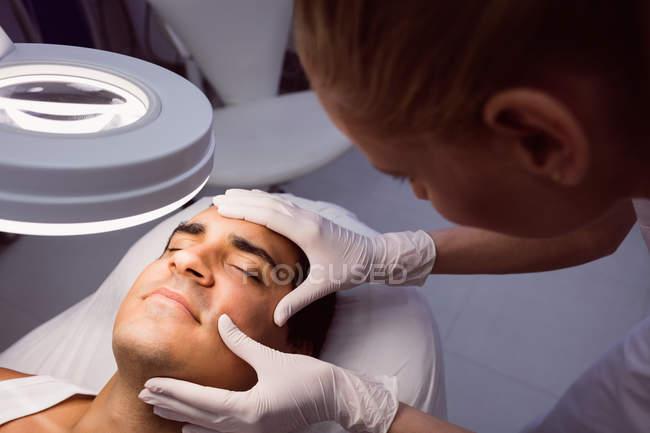 Arzt untersucht männliches Gesicht zur kosmetischen Behandlung in Klinik — Stockfoto