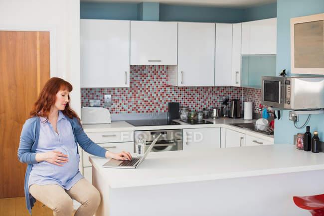 Femme enceinte utilisant un ordinateur portable dans la cuisine à la maison — Photo de stock