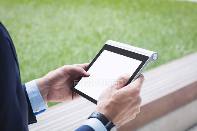Cropped image of businessman using digital tablet outside office building — Stock Photo