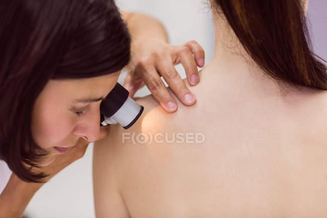 Dermatólogo examinando la piel del paciente con dermatoscopio en la clínica - foto de stock