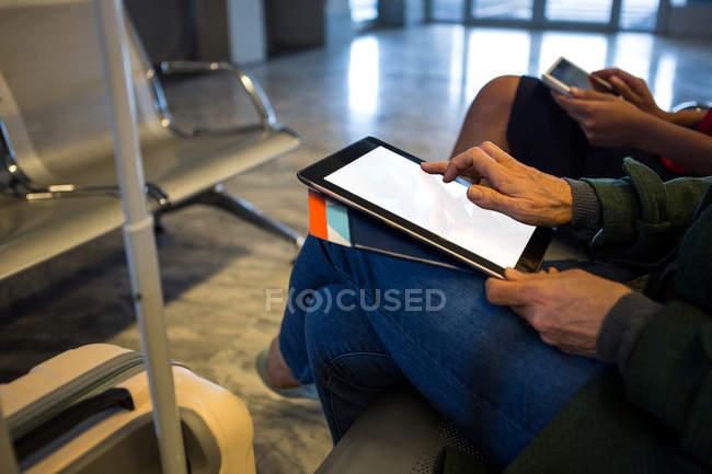 Средняя часть женщины, использующая цифровой планшет в зоне ожидания в аэропорту — стоковое фото
