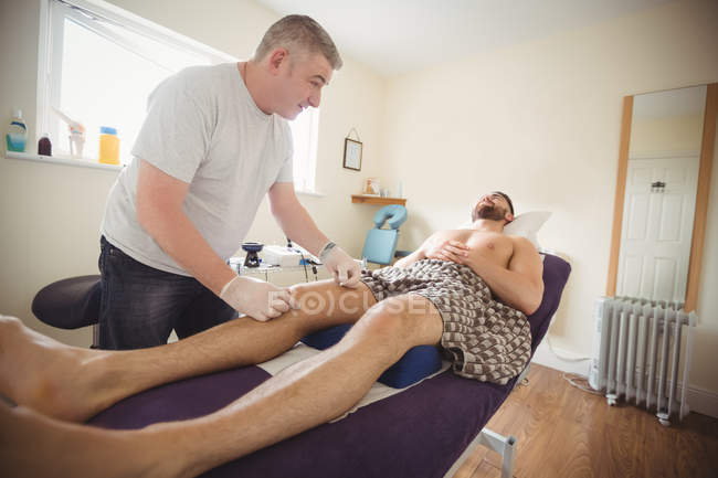 Physiotherapist performing dry needling on knee of male patient in clinic — Stock Photo