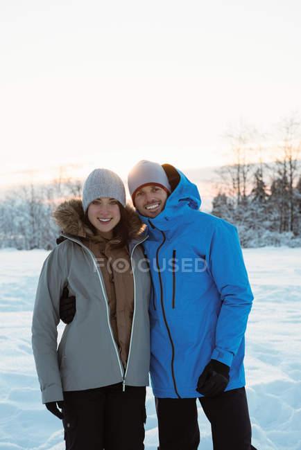Portrait de couple souriant debout sur un paysage enneigé — Photo de stock