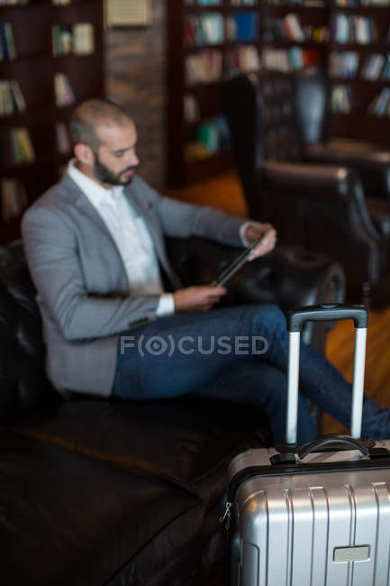 Businessman using digital tablet in waiting area at airport terminal — Stock Photo