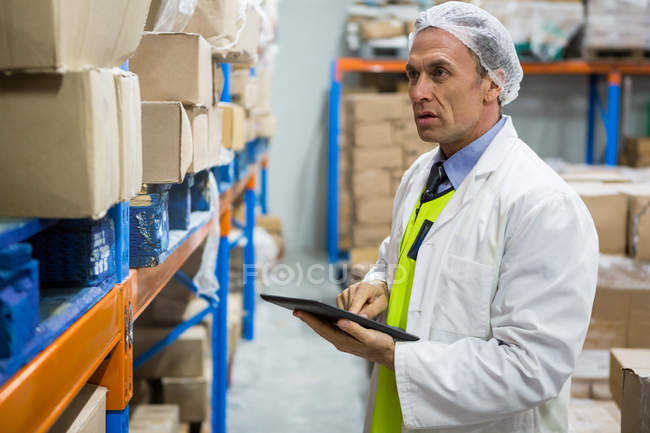 Technician maintaining record on digital tablet at meat factory — Stock Photo