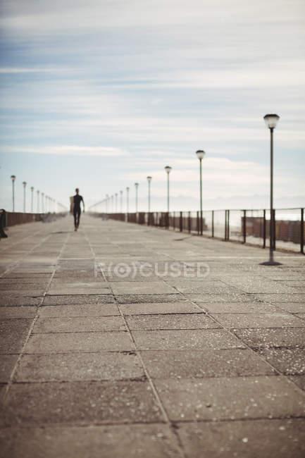 Vue lointaine du surfeur marchant avec planche de surf sur la jetée à la plage — Photo de stock