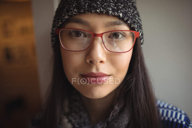 Portrait of beautiful woman wearing cap and spectacles in cafe — Stock Photo