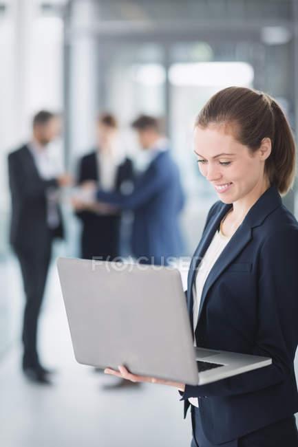 Donna di affari che sta nell ufficio e usando il portatile — Foto stock