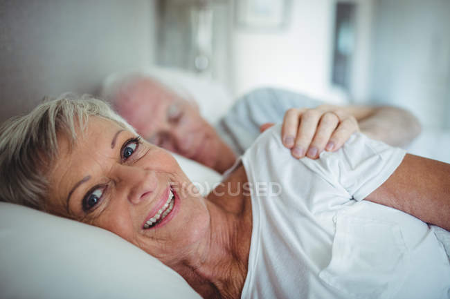 Senior couple lying on bed in bedroom — Stock Photo
