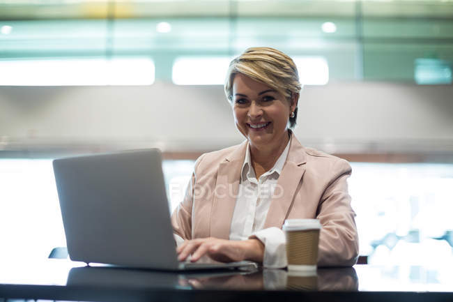 Portrait of smiling business woman using laptop in waiting area at airport terminal — Stock Photo