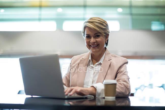 Портрет улыбается женщина бизнес, используя ноутбук в зоне ожидания в аэропорту терминал — стоковое фото