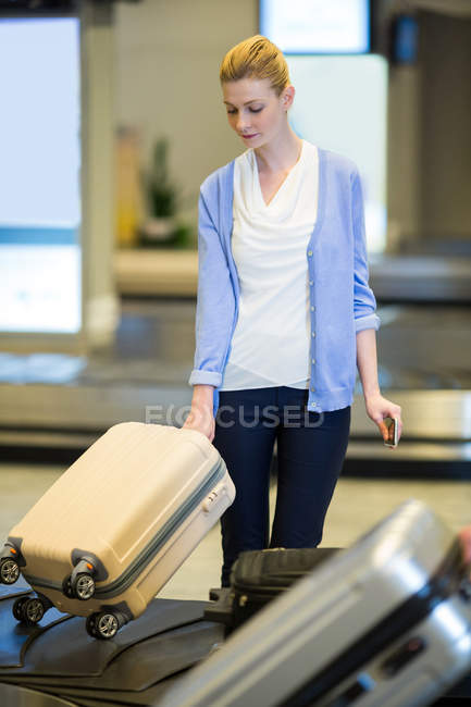 Businesswoman picking his luggage from baggage claim area at airport terminal — Stock Photo