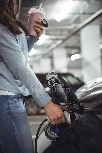 Section médiane de femme recharge voiture électrique à charge conductive pour véhicules électriques — Photo de stock