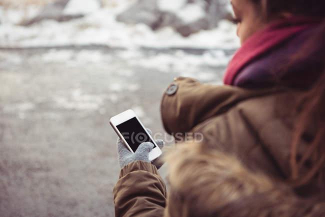 Gros plan de la femme utilisant un téléphone portable sur la rive de la rivière en hiver — Photo de stock